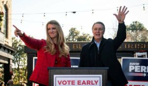 © Al Drago/Reuters Senators Kelly Loeffler (R., Ga.) and David Perdue (R., Ga.), wave during a campaign event in Milton, Ga., December 21, 2020.