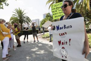 A small group of demonstrators gathers at Lake Eola Park to protest the Florida unemployment benefits system on June 10 in Orlando. Many jobless workers were left struggling to apply and receive unemployment benefits after the start of the coronavirus pandemic. (AP Photo/John Raoux) [ JOHN RAOUX | AP ]