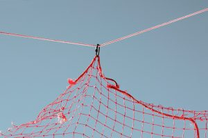 Close-up of a red net on a blue sky