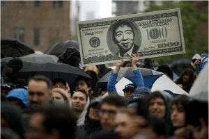 A man carries a sign supporting former Democratic presidential candidate Andrew Yang's plan for a $1000 monthly universal basic income. | Drew Angerer/Getty Images