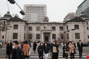 People wearing face masks walk by the headquarters of the Bank of Korea in Seoul, South Korea, Thursday, March 4, 2021. South Korea's central bank says the country's economy shrank for the first time in 22 years in 2020.