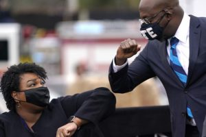 Democratic Senate candidate Raphael Warnock (R) bumps elbows with Stacey Abrams (L) during a campaign rally with U.S. President-elect Joe Biden at Pullman Yard on December 15, 2020 in Atlanta, Georgia.