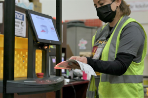 A warehouse worker for Superior Uniform Group scans a shipment label on a collaborative mobile robot from 6 River Systems at a facility in Coppell, Texas. PHOTO: 6 RIVER SYSTEMS
