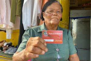 Jandira Freitas shows off her mumbuca card — aid in the form of digital currency — that helped her start her own small business in the socialist city of Marica, Brazil, where she lives [Monica Yanakiew/Al Jazeera] By