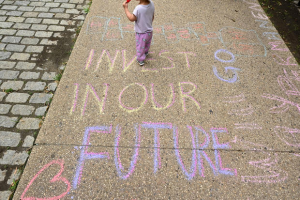 Sidewalk chalk drawings by parents and children to celebrate new monthly Child Tax Credit payments, and urging Congress to make them permanent, outside the home of New York state Senator Charles Schumer on July 12, 2021, in Brooklyn, New York.  BRYAN BEDDER/GETTY IMAGES FOR PARENTSTOGETHER)