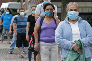 Residents wearing protective masks due to the coronavirus outbreak wait in line for boxes of donated food in Chelsea, Mass.    Charles Krupa / AP