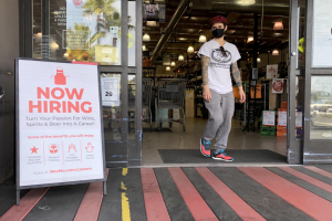 A customer walks by a now hiring sign at a BevMo store on April 02, 2021 in Larkspur, California. (Photo by Justin Sullivan/Getty Images)